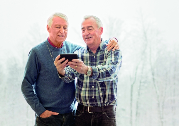 Senior gay couple shooting a selfie with mobile phone